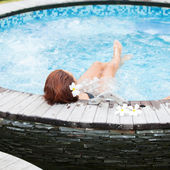 Beautiful woman relaxing in jacuzzi at spa centre — Stock Photo