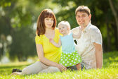 Happy family. Mother, father and daughter in the park — Stock Photo
