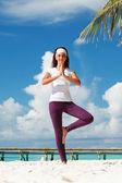 Pretty woman doing yoga exercises on the tropical beach — Stock Photo