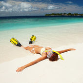Cute woman with snorkeling equipment relaxing on the tropical be — Stock Photo