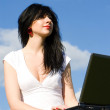 Pretty woman with laptop on sky background — Stock Photo #9251130