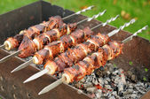 Skewers of liver with onions and bacon on the grill — Stock Photo