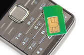 Mobile phone and a SIM card, white background — Stock Photo