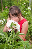 Smiling girl among the flowers — Stock Photo