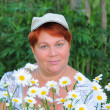 Middle-aged woman next to flowers daisies — Stock Photo