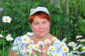 Middle-aged woman next to flowers daisies — Стоковое фото