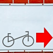 The Guide post park bicycle with red arrow on brick wall background — Stock Photo #11882620