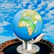 The Sculpture of world in hand on blue sky background - Stock Photo