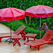 Wooden bed with umbrellat pool — Stock Photo #12656234
