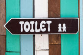 Sign restroom of men and women on wood background — Stockfoto