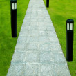 The Stone block walk path with garden lamp on green grass backgr — Stock Photo #13149275