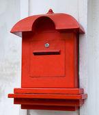 Czerwony postbox na tle białej ściany — Zdjęcie stockowe