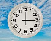 White Clock isolated on blue sky backgroun — Stock Photo