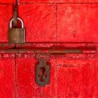 Old master key and old bolt on red wooden door — Stock Photo #32543413