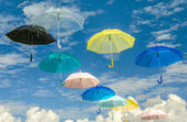 Multicolored umbrellas against blue sky background — Stock Photo