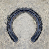 Rusted horseshoe on floor background — Stock Photo