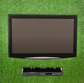 Artificial green grass with lcd screen with dvd — Stock Photo