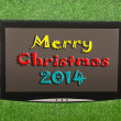Stock Photo: Lcd screen on artificial green grass of merry christmas 2014