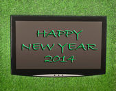 Lcd screen on artificial green grass of happy new year 2014 — Stock Photo