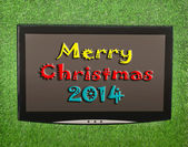 Lcd screen on artificial green grass of merry christmas 2014 — Stock Photo
