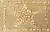 Star of pebbles on cement floor — Stock Photo