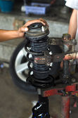 Auto car mechanic working on car shock absorber in car service w — Stockfoto