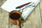 Cup of coffee with notebook — Stock Photo