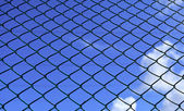 Metal mesh and blue sky — Stock Photo