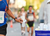 Marathon racer catching cup of water — Stock Photo