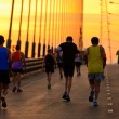 Runners run on bridge in the morning - Stock Photo