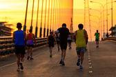 Runners run on bridge in the morning — Stock Photo
