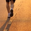 Feet of runner in evening light - Stock Photo