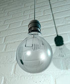 Hanging Light Bulb And Fitting On A Wall — Stock Photo