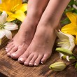 Female feet with spa pedicure and flowers — Stock Photo