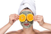 Beautiful woman with facial mask and oranges — Stock Photo