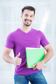 Teenage student with folders and thumb up — Stock Photo