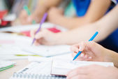 Students writing in classroom, close up — Stock Photo