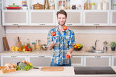 Cheerful young man juggling tomatoes while preparing food in kitchen — Stock Photo