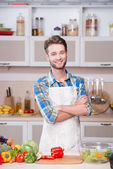 Smiling man cooking dinner in kitchen — Stock Photo