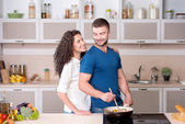 Beautiful couple preparing supper and looking at each other — Stock Photo