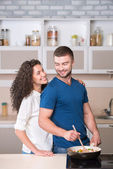 Happy couple preparing supper and looking at each other — Stock Photo