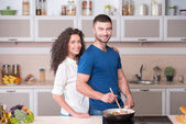 Beautiful couple preparing supper together in kitchen — Stock Photo
