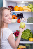 Woman choosing apple in refrigerator full of tasty organic nutrition — Stock Photo