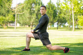 Young sportsman doing stretching exercise outdoors — Stock Photo