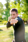 Sportsman showing kick with the fist, close up — Stock Photo