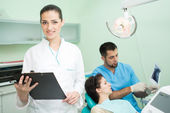 Dentist and his assistant at work — Stock Photo