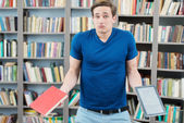 Confused student trying to choose between book and computer — Stock Photo