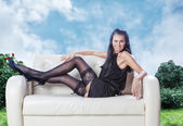 Sexy brunette laying on a couch wink in black dress on a garden — Stock Photo