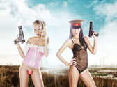 Two sexy girls bottomless in underwear holding a gun on a city b — Stock Photo