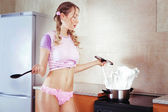 Sexy housewife cooking milk splash in a pot at the kitchen — Stock Photo